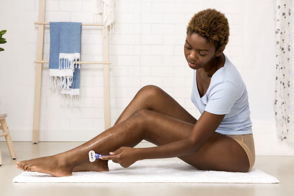 Woman Shaving Her Legs in a Bathroom