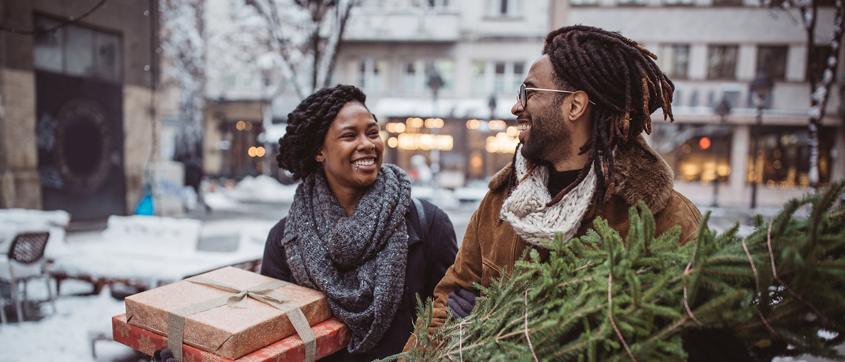 woman holding presents next to man holding tree outside in a downtown setting