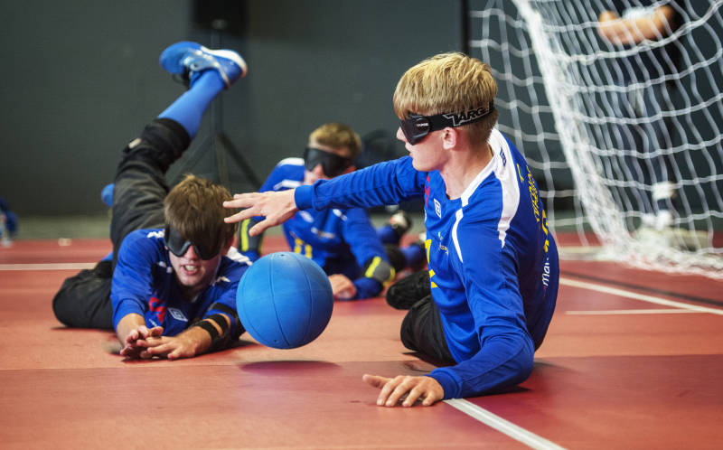 Ett goalballag med tre killar ligger ner en kille har stoppat bollen från att gå in i mål.