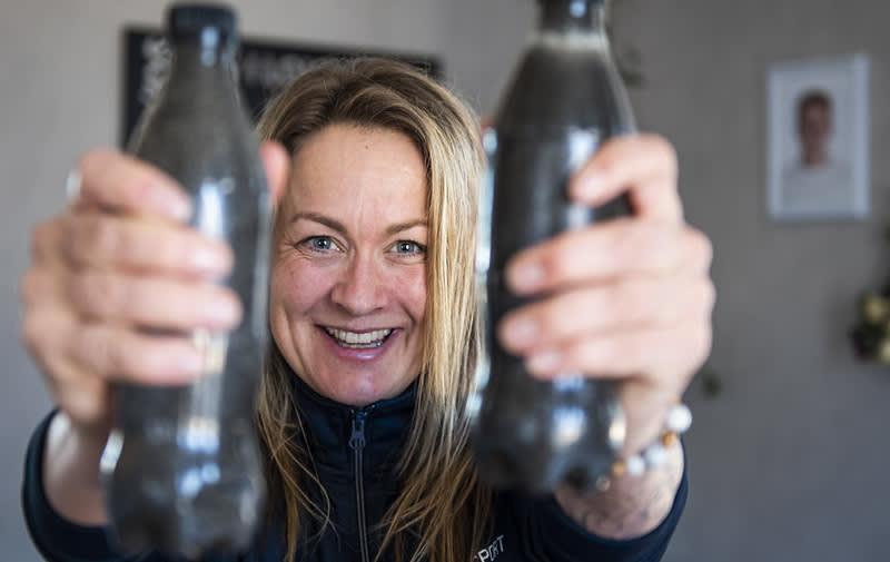 En kvinna håller upp två fyllda petflaskor framför kameran och ler.