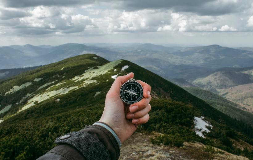 Person using a compass in the wilderness