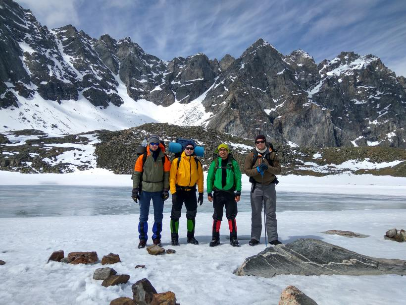 Four friends posing for a photo in the snow in front of a mountain and lake