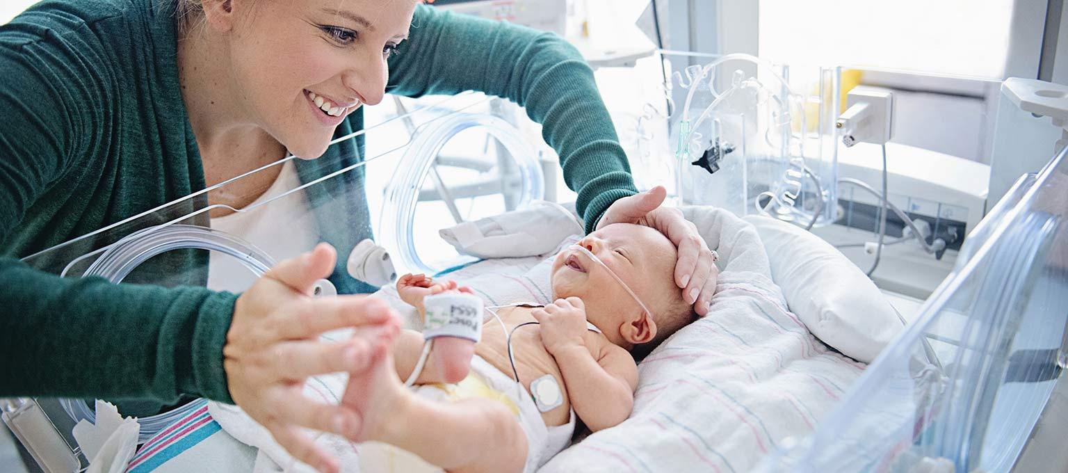 Мама с недоношенным ребенком в инкубаторе
