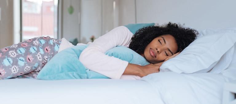 Испытывающая тошноту женщина лежит в постели