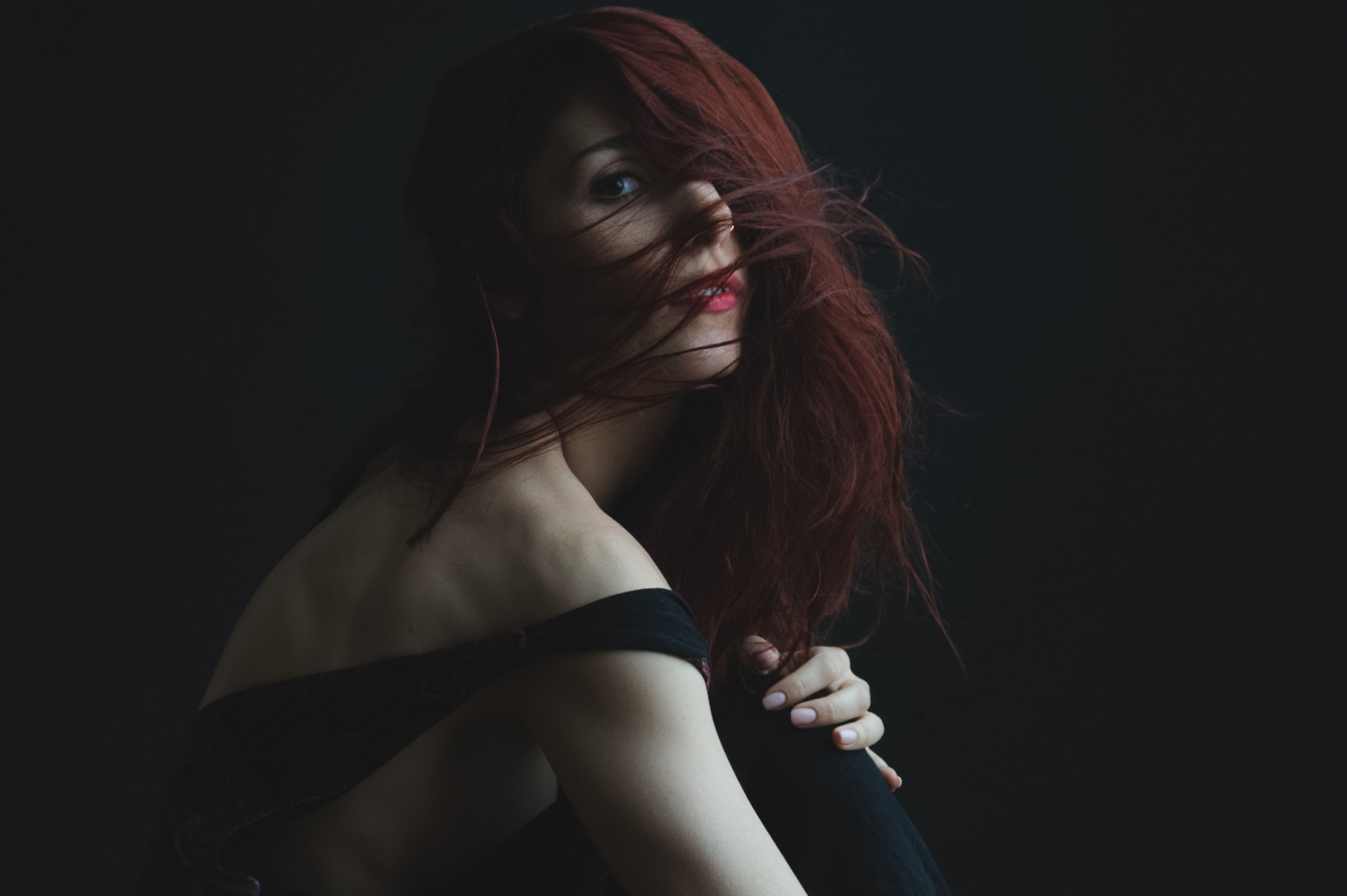 a portrait of Jana sitting in front of a black background with her dark red hair flowing in front of her face looking slightly towards the camera, her skin is light and you can clearly see the definition of her muscles.