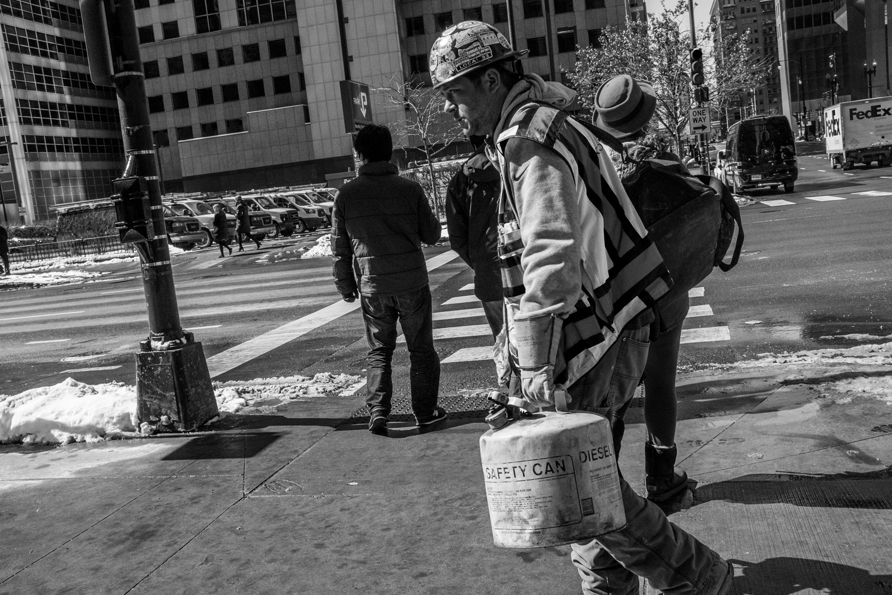 a black and white shot of a construction worker walking with stickered helmet on his head a high visibility vest on, some kind of fuel or gas can in his hands and a  backpack slung over his shoulder.