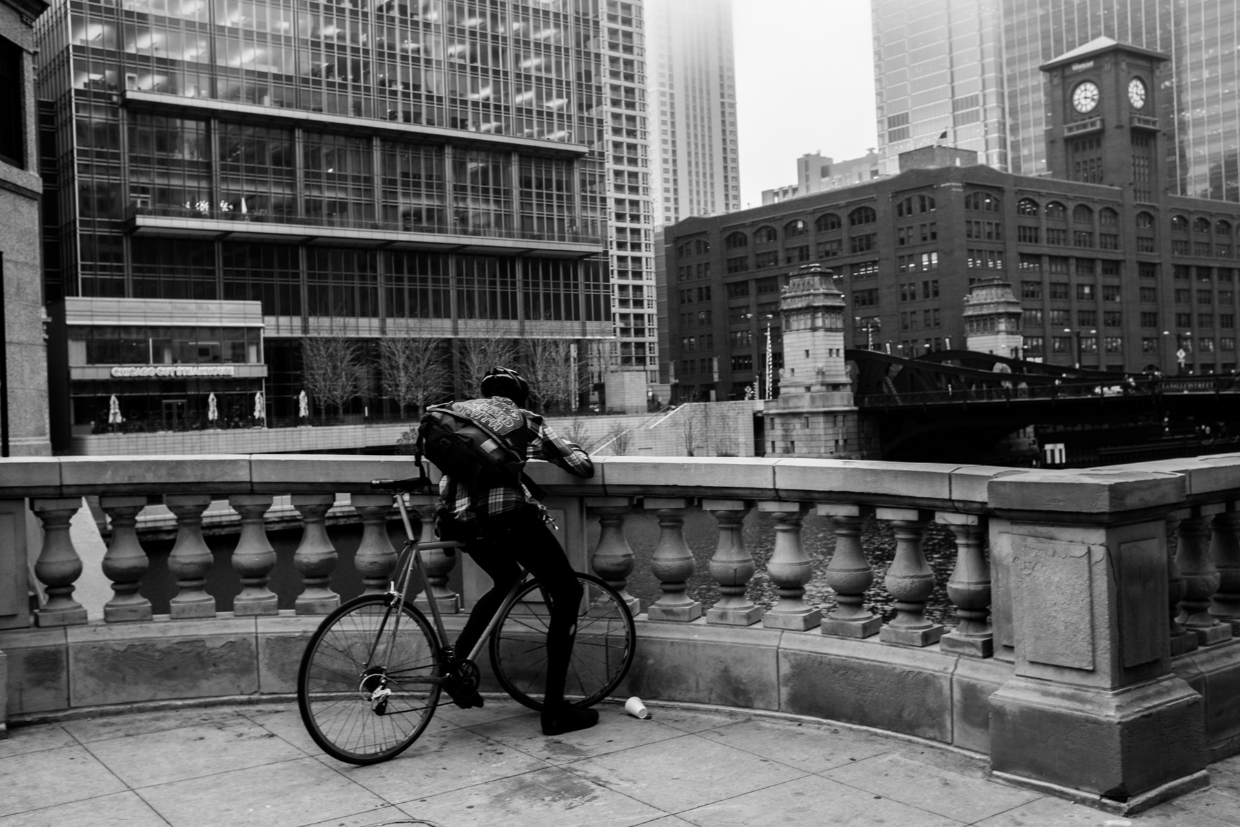 from my bike messenger series. A shot of a messenger sitting at the side of the Chicago river downtown Chicago taking a well deserved break to swipe through social media.