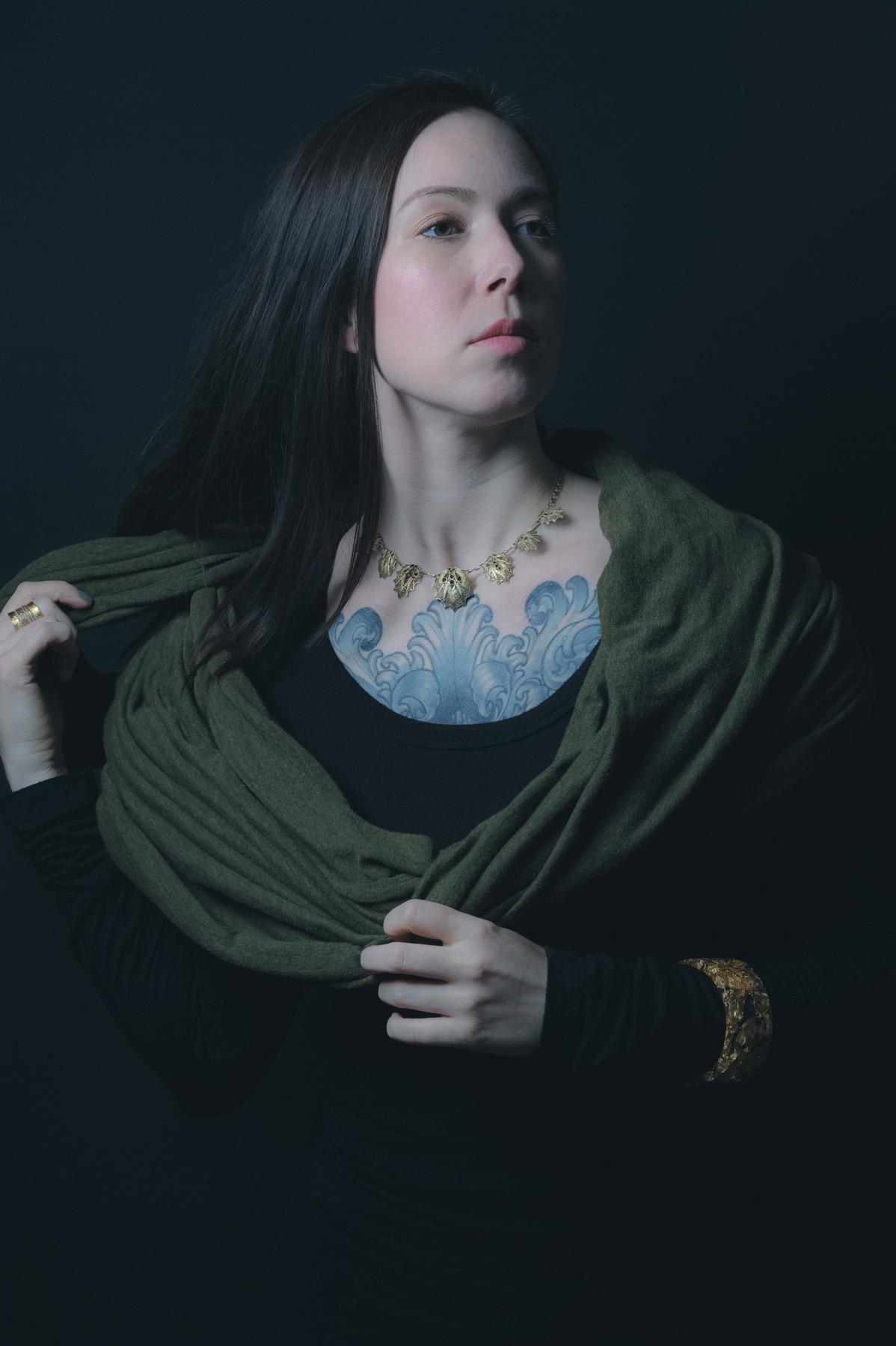 A portrait of Amelie wearing a black top with an ornate gold band around her left forearm, with a green scarf around her shoulder. she is in front of a black background.