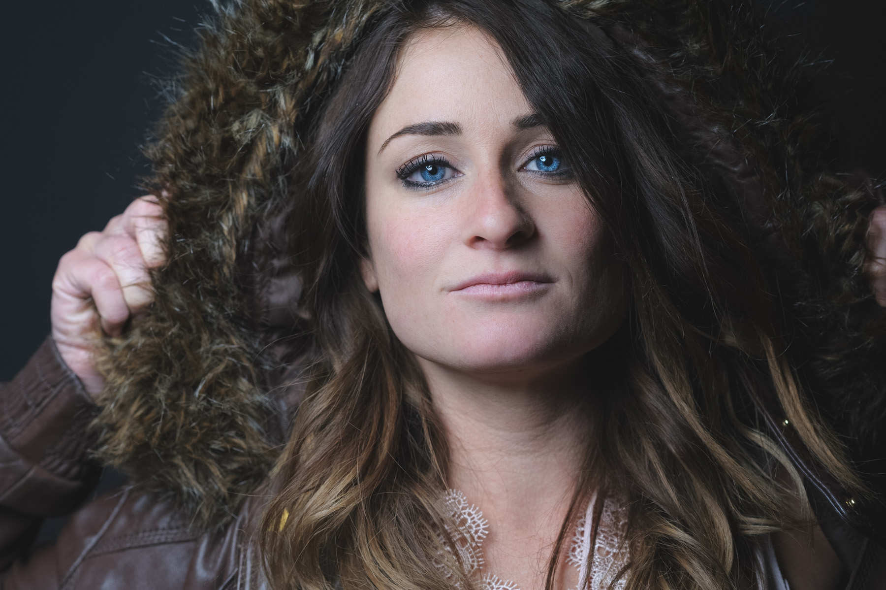 a close up portrait of my friend Ashley wearing a brown park with the fur trimmed hood over her head and her blue eyes looking directly at the camera.