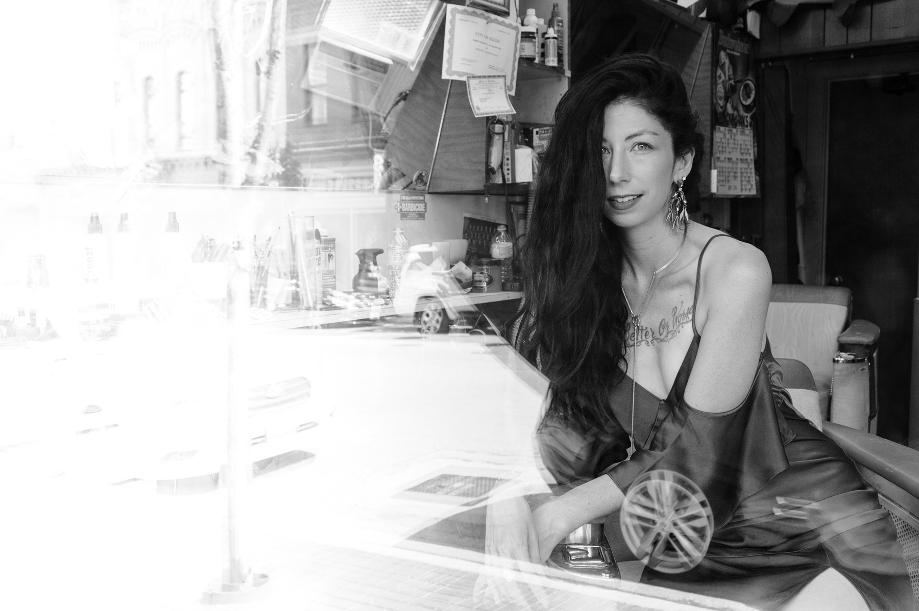 Black and white portrait of Jennifer sitting in a chair of a classic barber shop shot through a window
