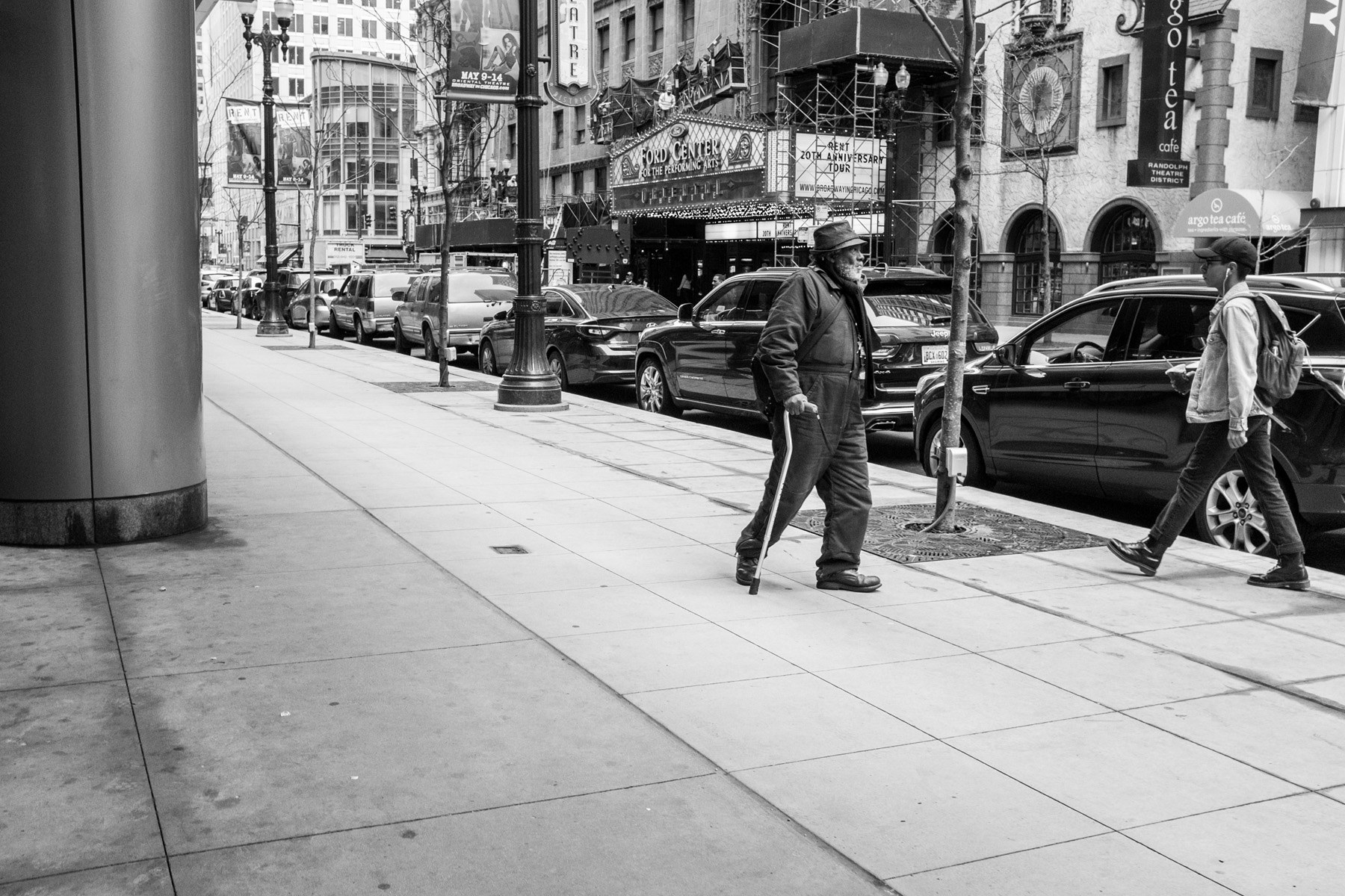 an older man bundled up walking through downtown Chicago with a cane.