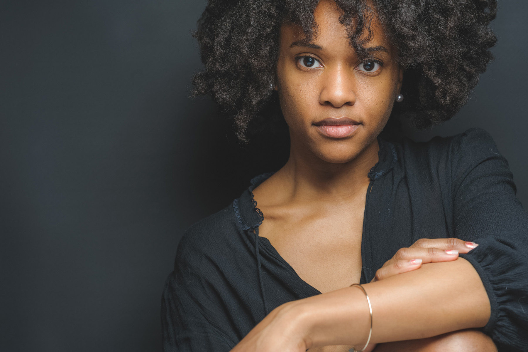 portrait of photographer and dancer Michelle Reid sitting in front of a black background wearing a black top with a gold bracelet on her wrist.