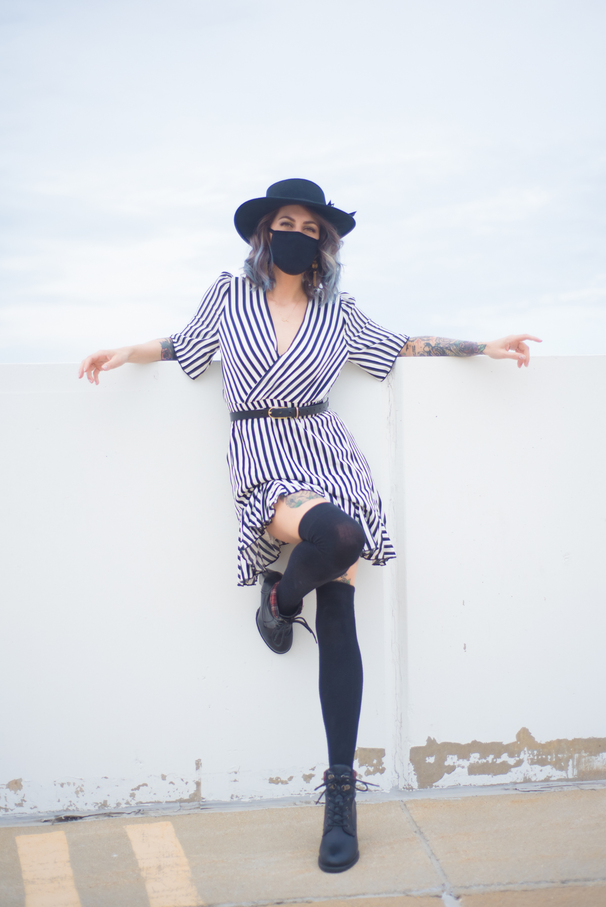 a portrait of Christina wearing a striped dress, knee high black socks and black mask and hat.