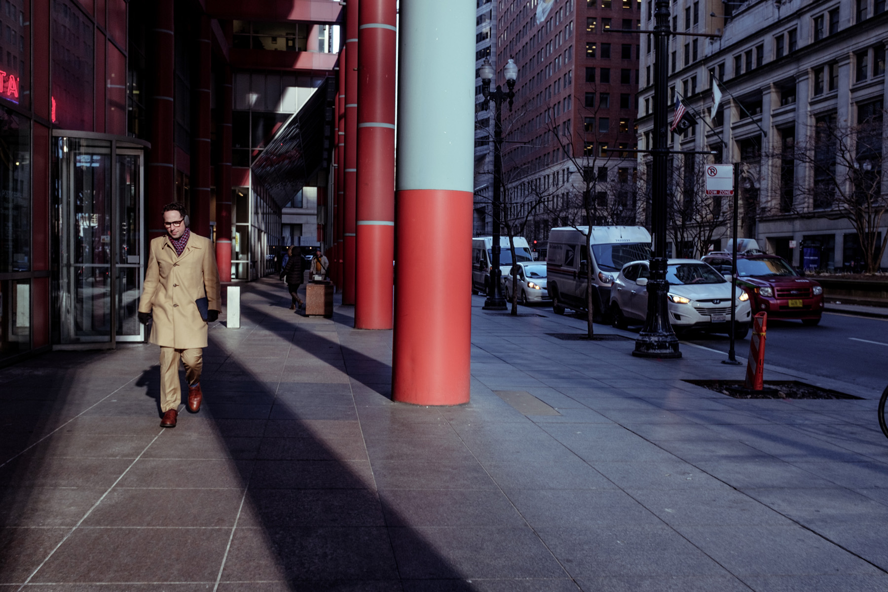 man walking just outside of the Thompson center framed to the right by the red and blue pillars.