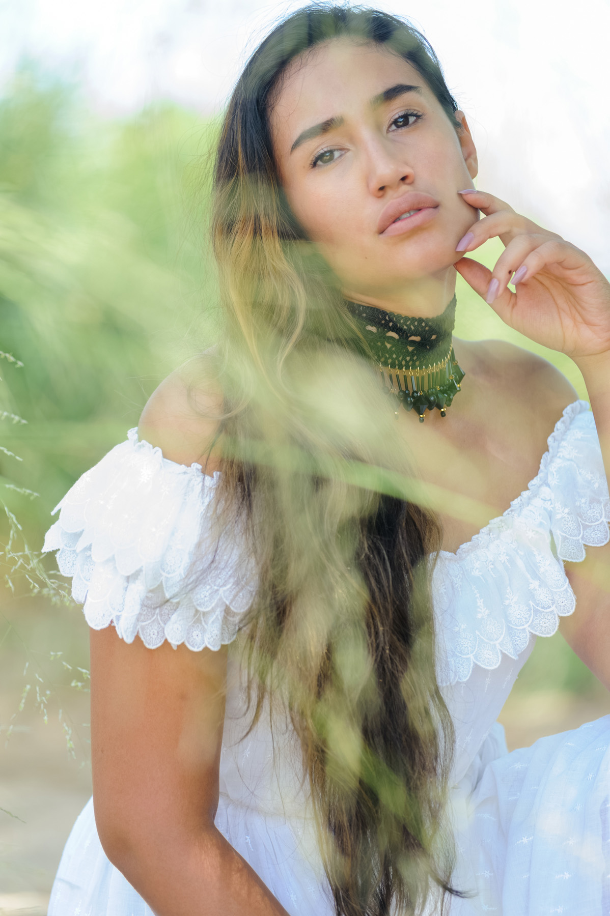 portrait of Shari, a woman wearing a white dress with long brown hair with tall green grass blurred in front of her