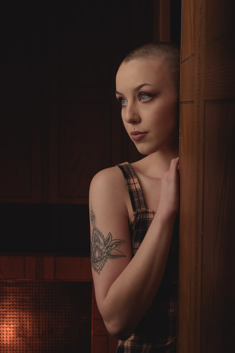 portrait of Marybeth in a dark  wood paneled room peaking around a door frame and lit with a single strobe from just out of frame in front of her.