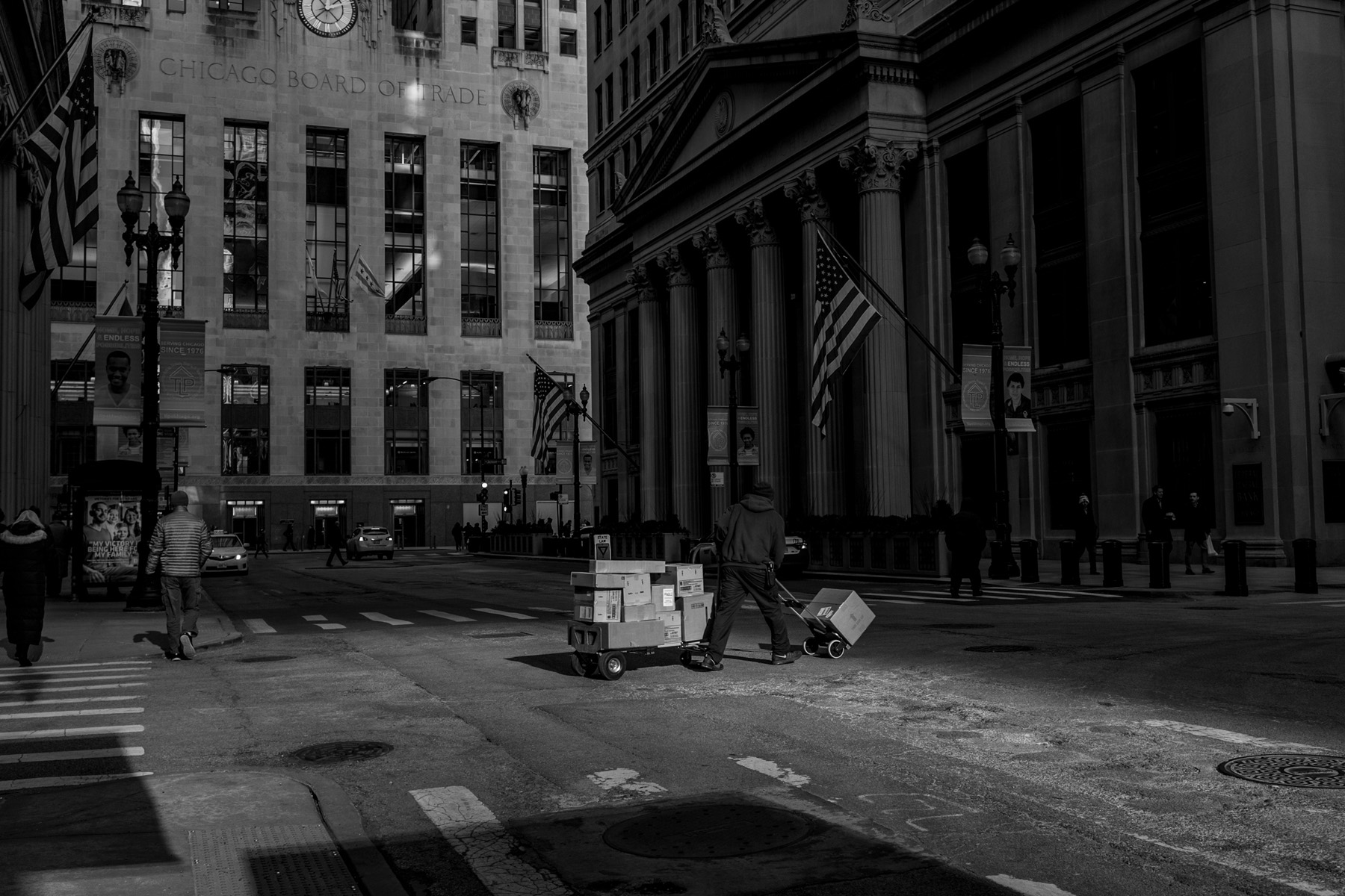 Post delivery man crossing the street in the financial district of Chicago (Black and White)