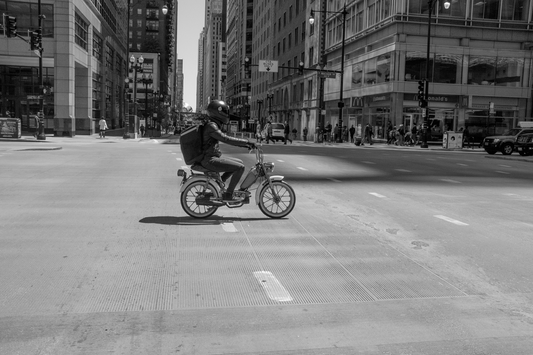 a motorcycle helmet wearing commuter riding a moped in downtown chicago.