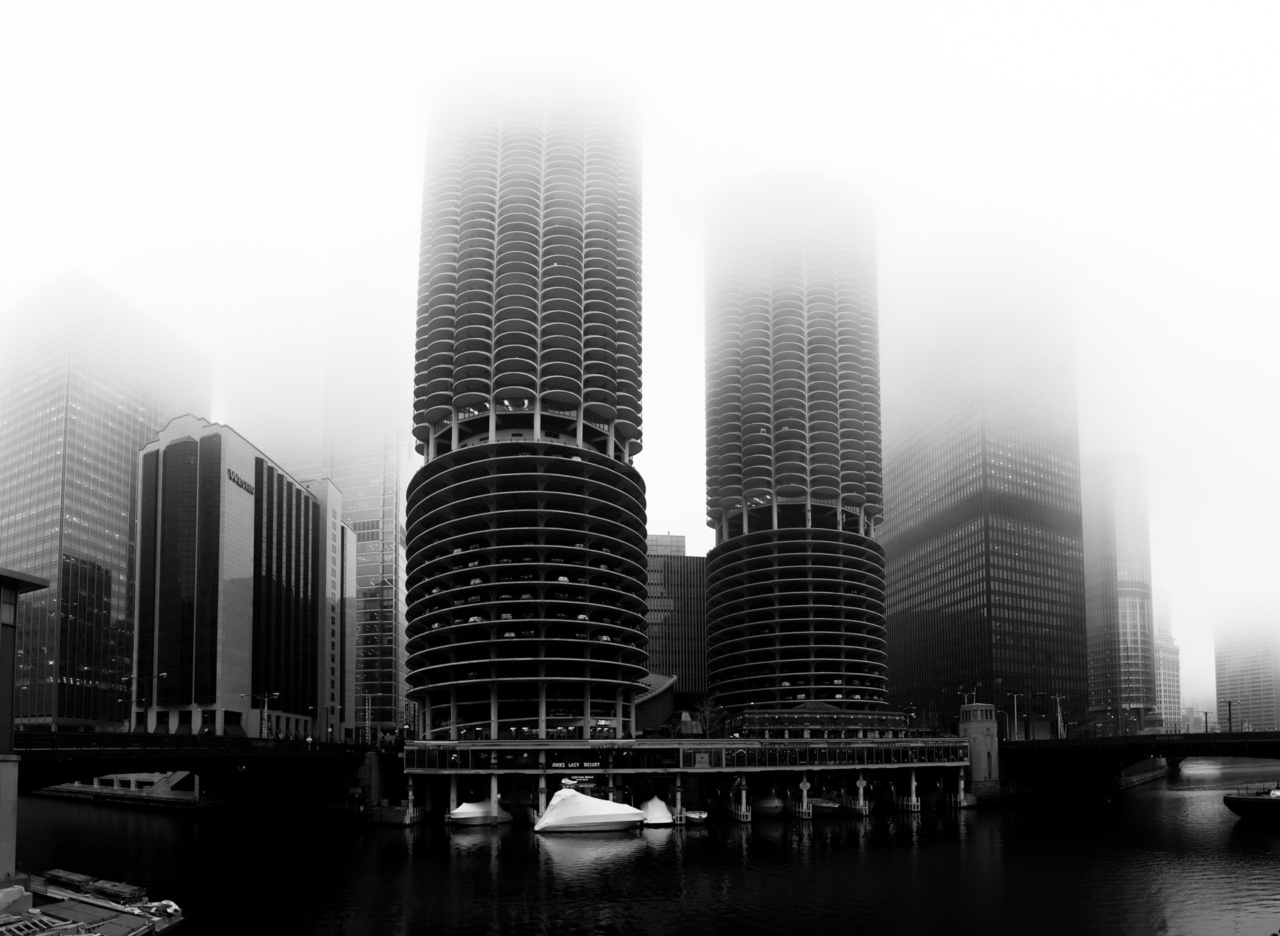 a black and white shot of the two towers of Marina city enveloped in fog.