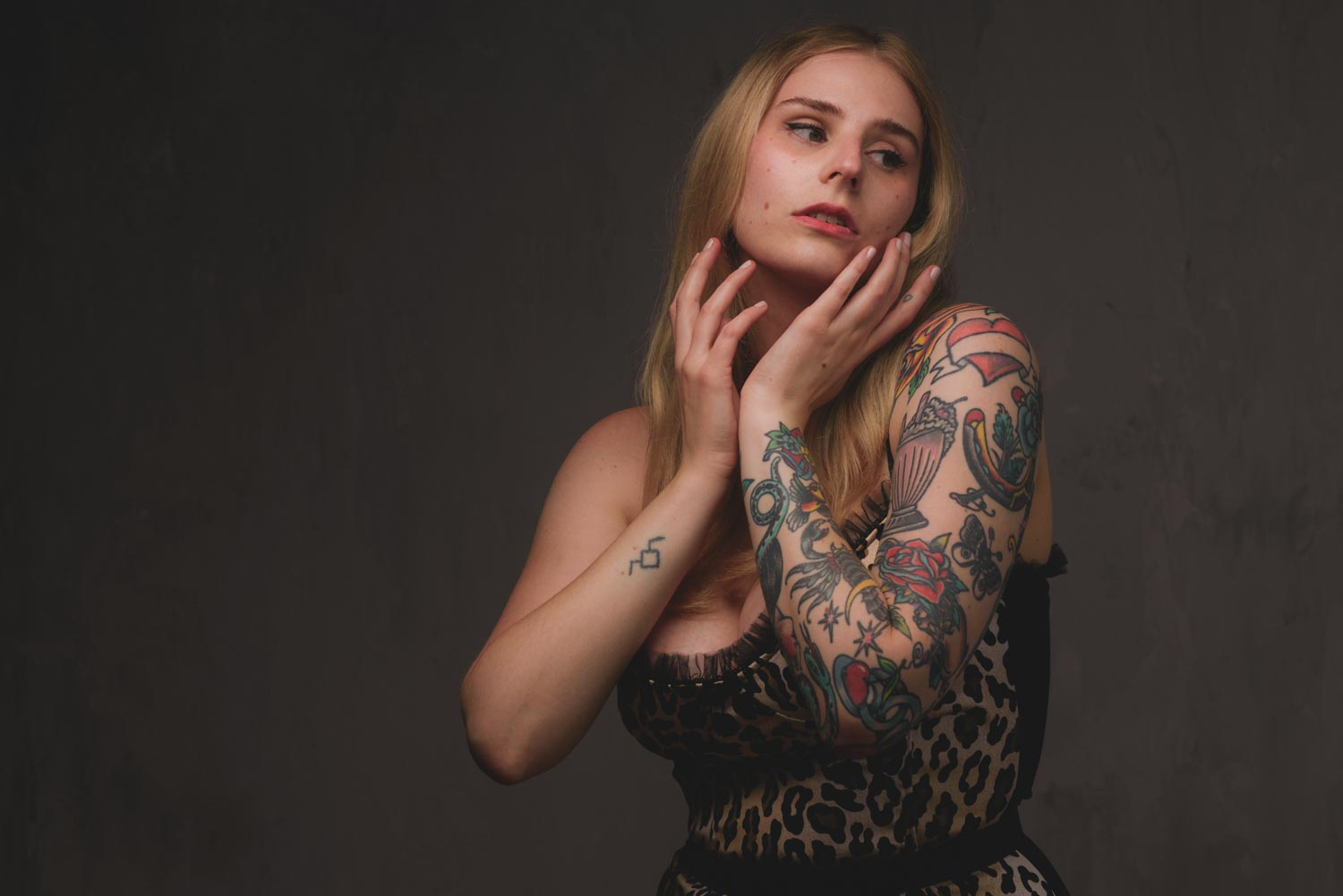a portrait of Allison in front of a concrete textured wall, she is holding her hands to her face and looking off away from the camera and she is wearing a leopard print dress.