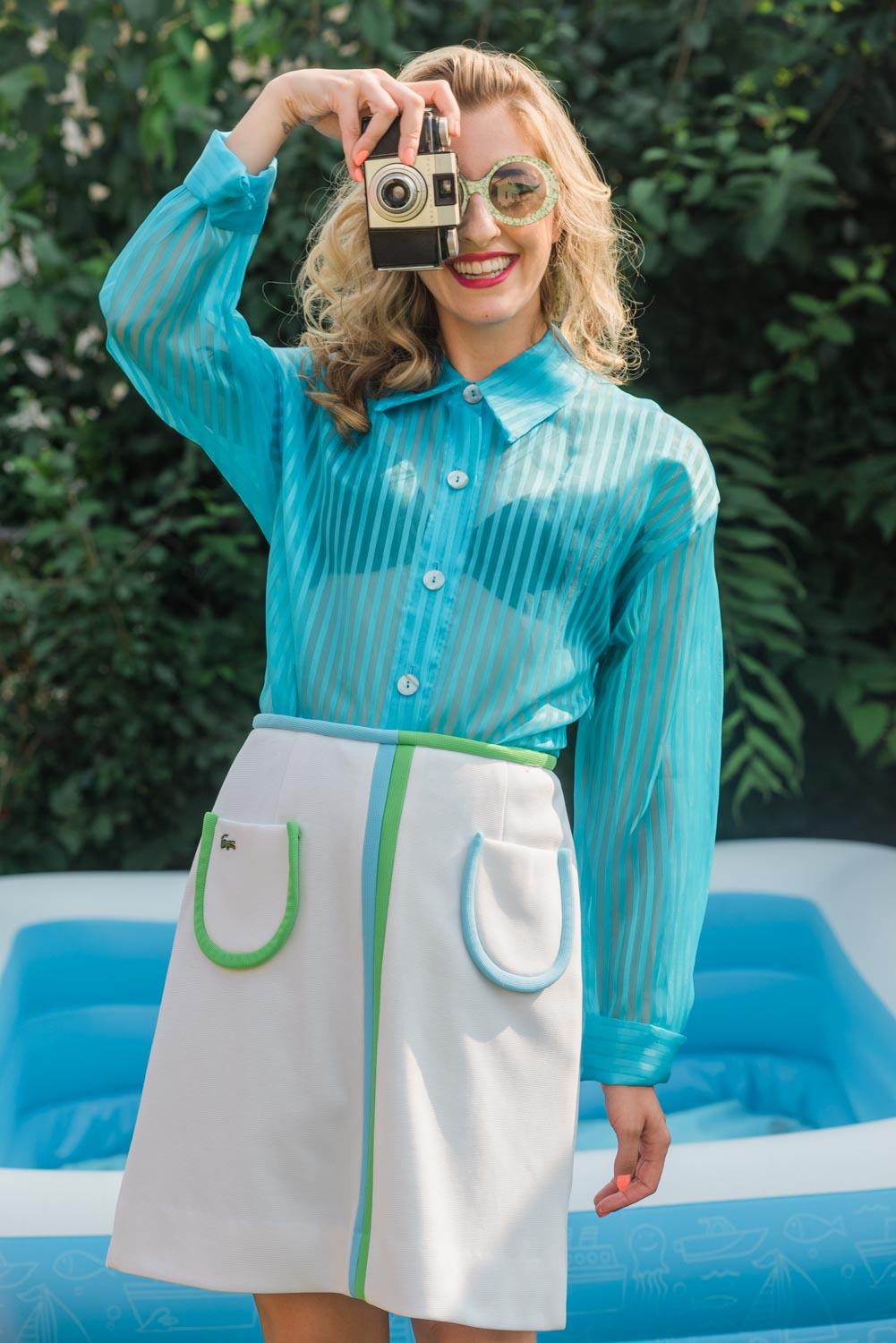 portrait of Amanda in a vintage sheer blue pin striped shirt and white skirt trimmed in white holding a vintage kodak camera