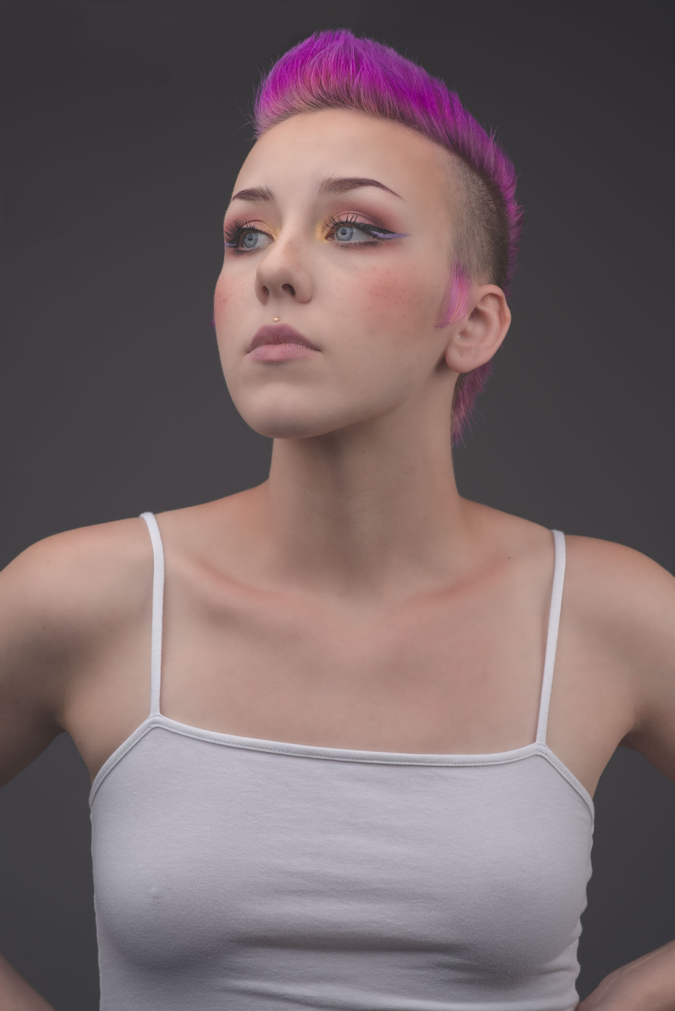 a portrait of Marybeth wearing a white tank top and a purple pink mohawk styled hairdo.