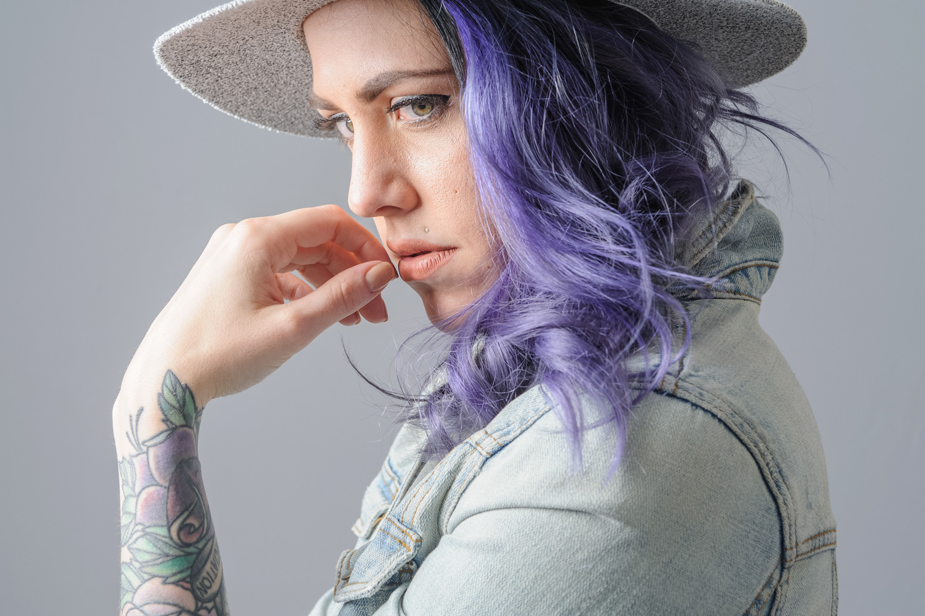 a portrait of Christina with purple hair and wearing a wide brim grey hat and faded blue jean jacket.