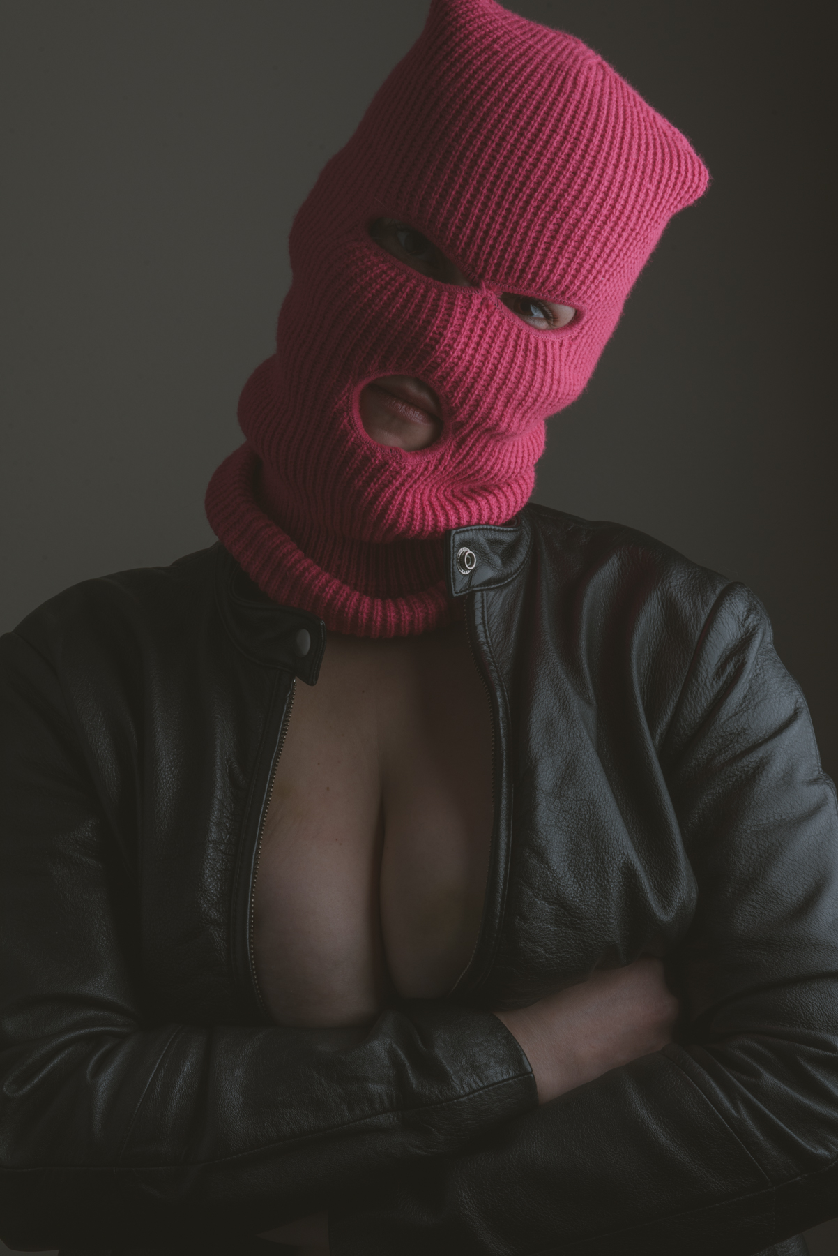 a portrait of a model wearing only a black leather jacket and a pink ski mask crossing her arms under her chest.