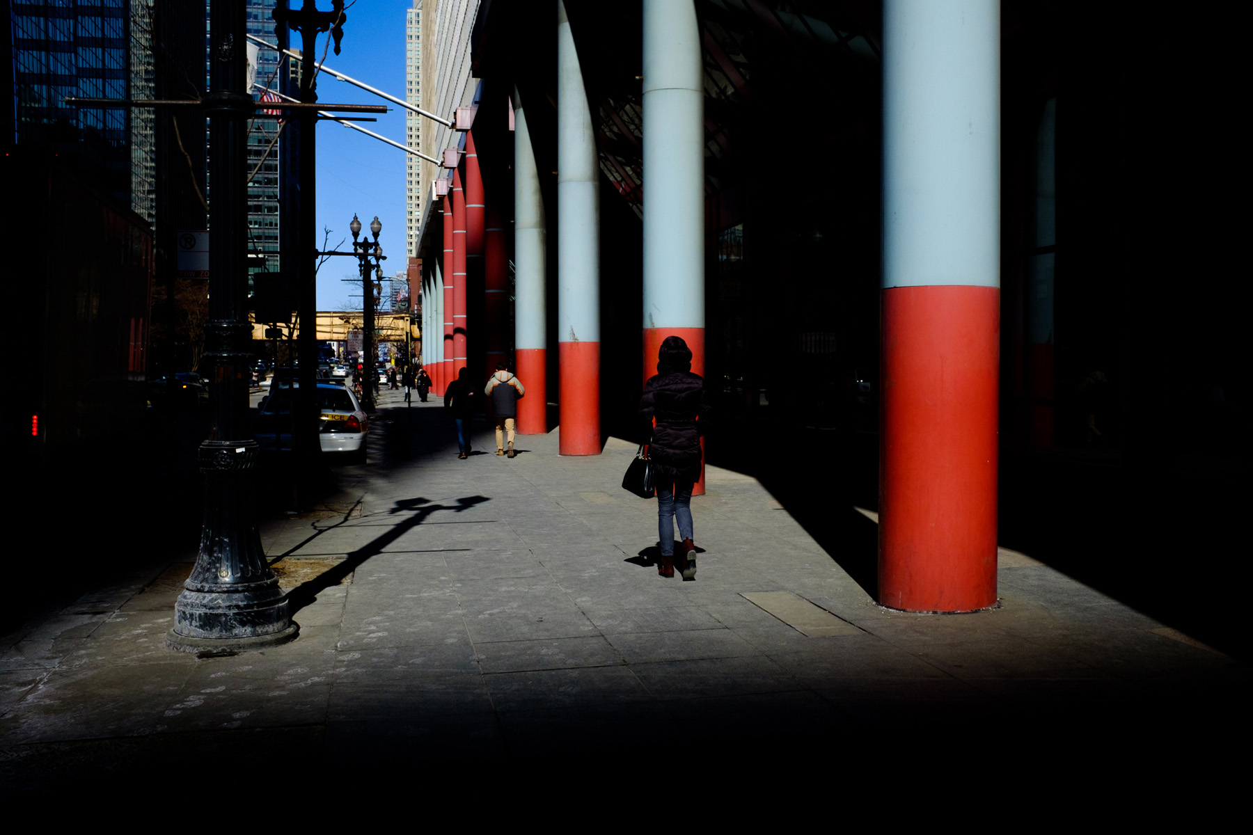 woman standing near the blue and red pillars of the Thompson Center surrounded by deep shadows.