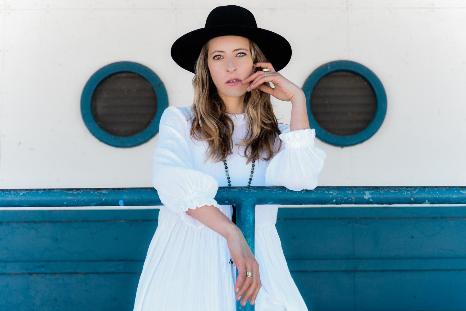 A portrait of Amanda wearing a white dress and black hat shot on a warm winter day at the boat house on Montrose beach in Chicago