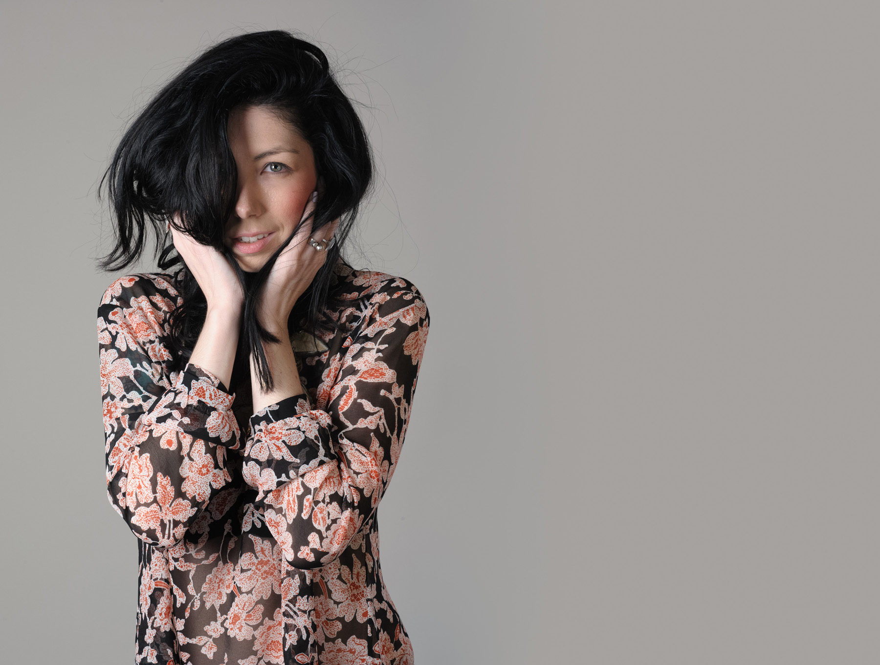 a portrait in studio of Jennifer wearing a sheer flower patterned blouse with her hand on her face holding her long dark hair in front of her right eye.