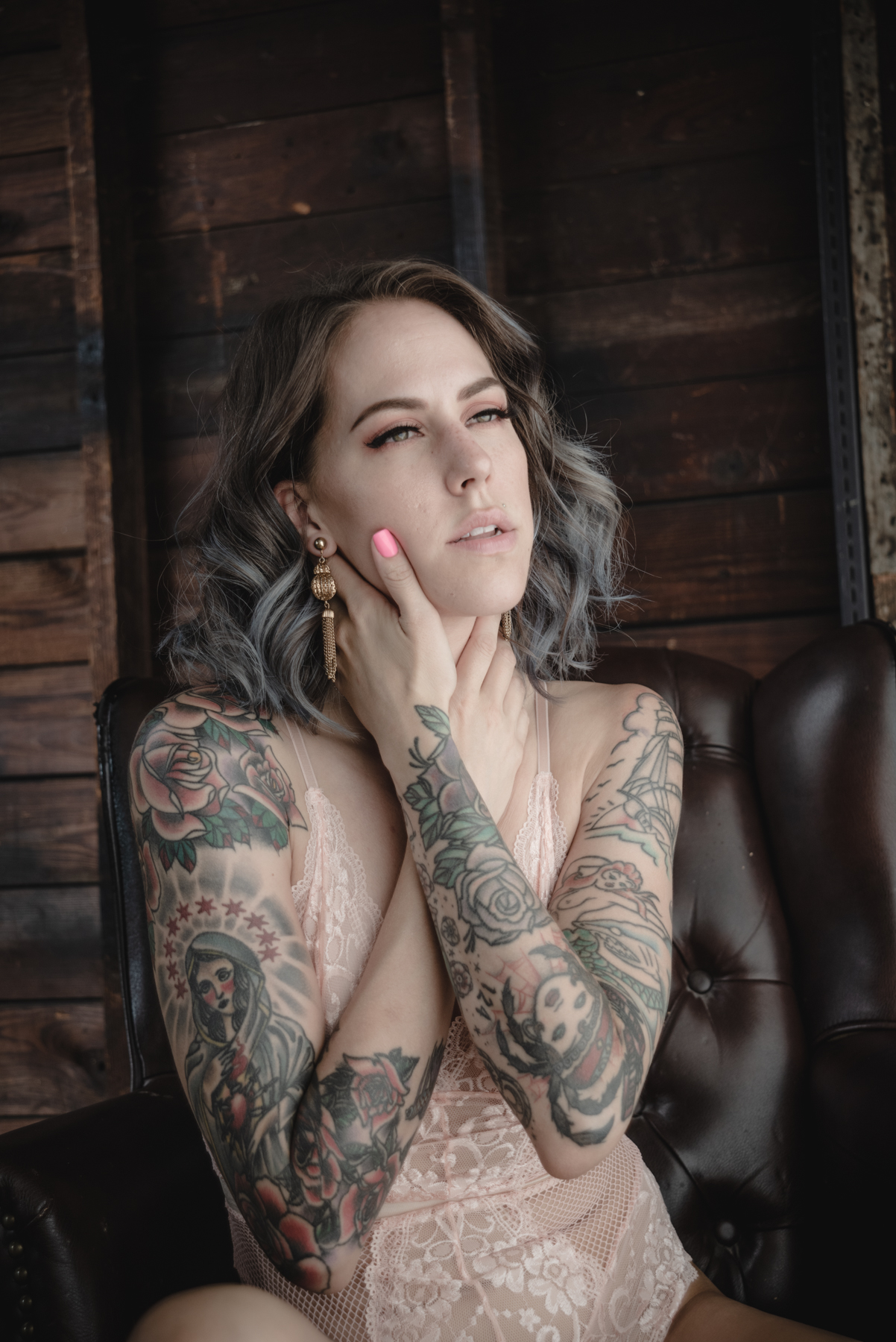 a portrait of Christina wearing a pink lace bodysuit sitting in a faux leather brown arm chair in front of a rough garage wooden wall.