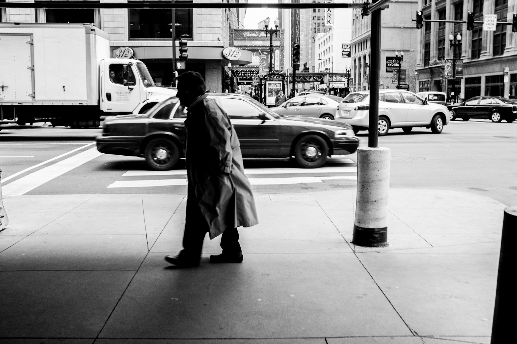 a black and white shot of an older gentleman in deep shadow walking in downtown Chicago with a slight slouch.