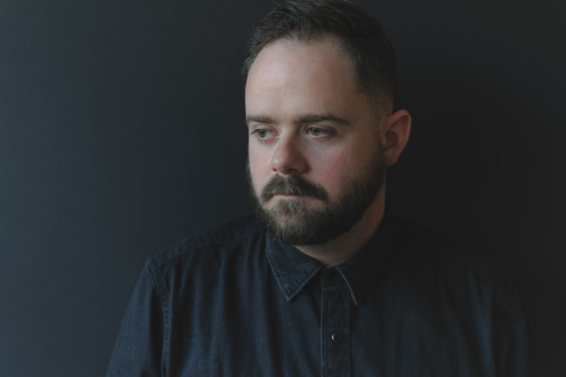 a portrait of Christopher on a black background wearing a black denim shirt, he has a forlorn look on his face and is looking off slightly away from the camera.