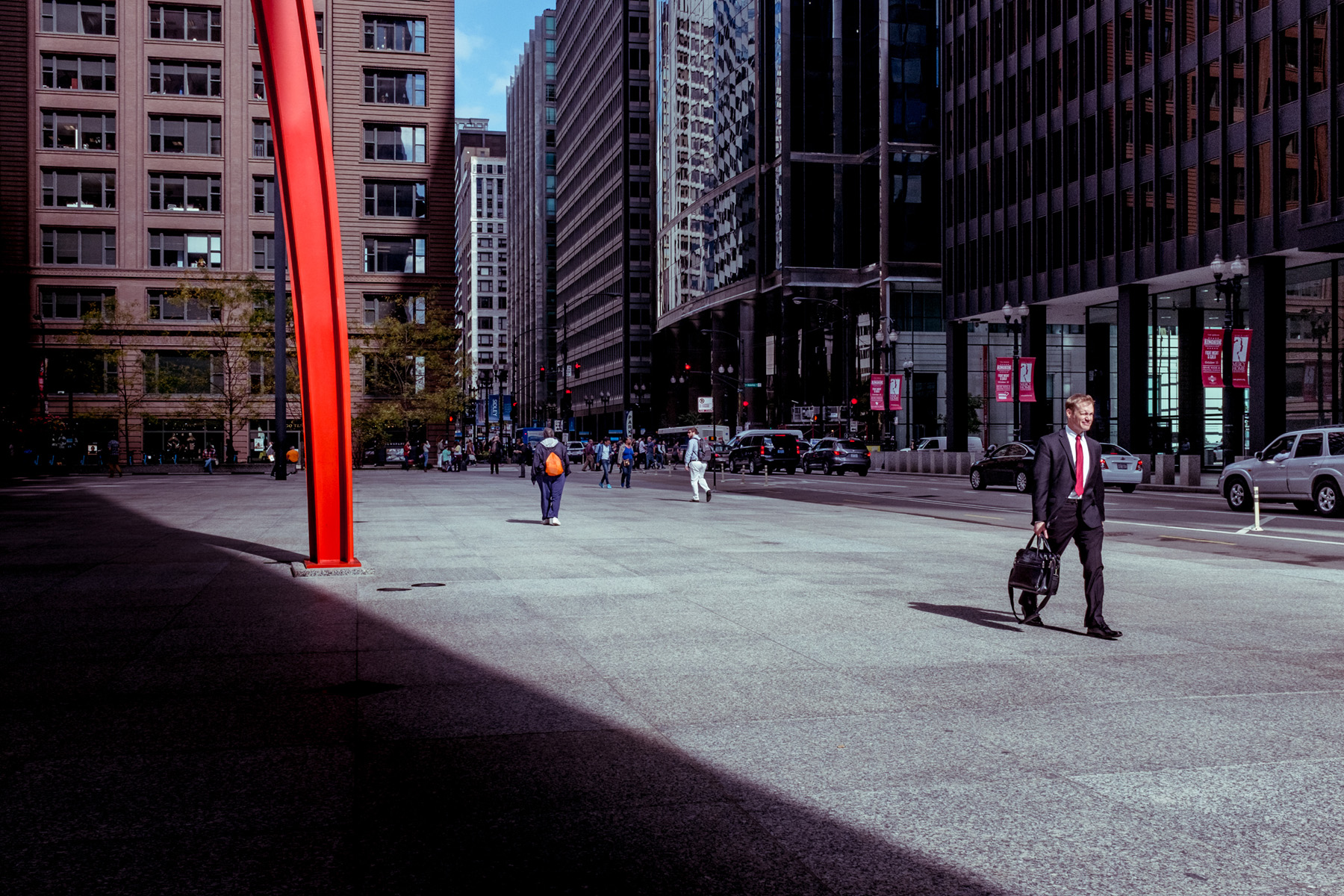 a photo of a man in a suit with a red tie, he is walking through Federal plaza and you can just see to the left of frame one of the legs from Calder's Flamingo.