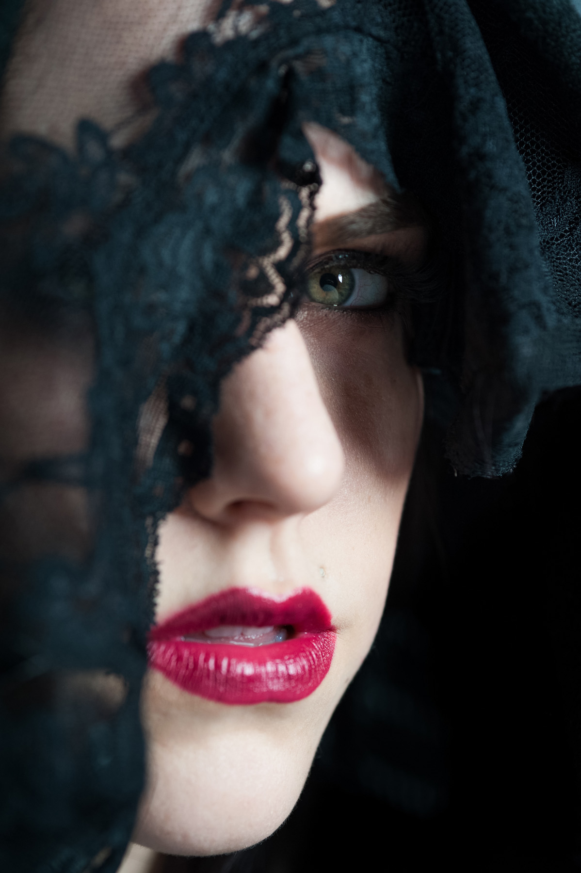 A close up color portrait of Christina wearing a black veil partially obscuring her face and you can clearly see her left eye a bright green color and her bright red lips set against her pale skin.