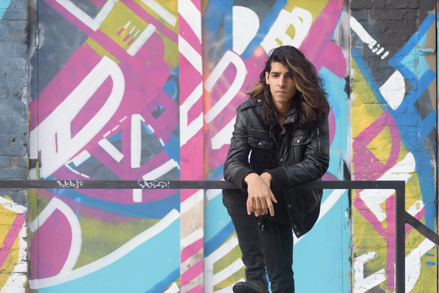 portrait of Matthew James Rao leaning against a railing towards the camera wearing a black leather jacket and pants in front of a pink, blue, yellow, and white graffiti wall