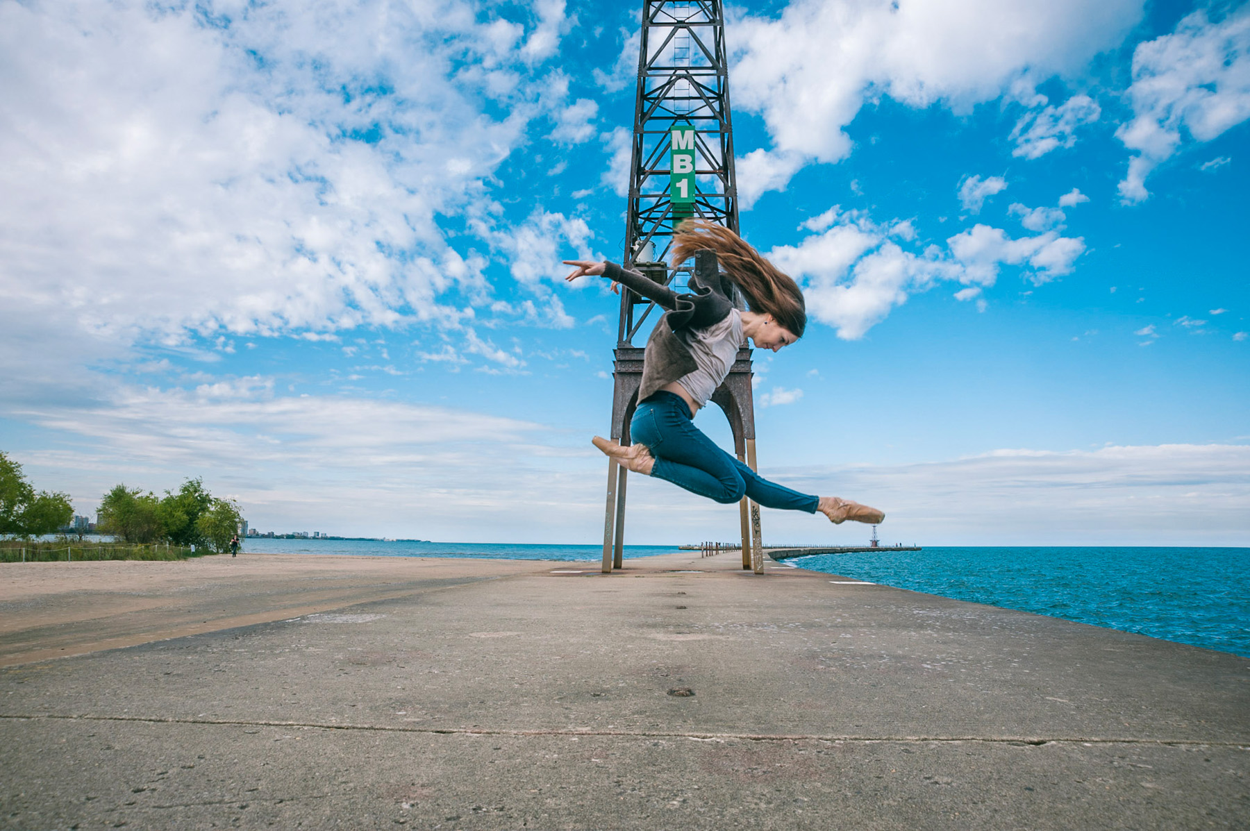 photo of dancer Elizabeth Cohen in mid air on a dock in Chicago with a beautifully blue cloudy sky and a tower in the background