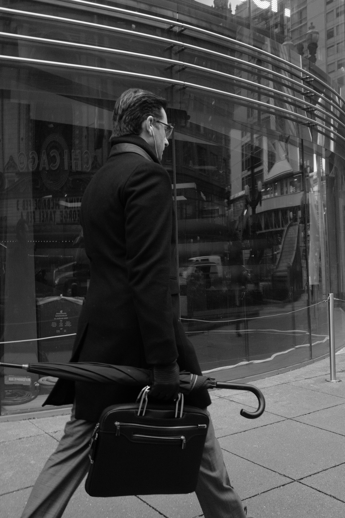 man wearing a black dress coat holding a briefcase and umbrella walking bristly to the right.