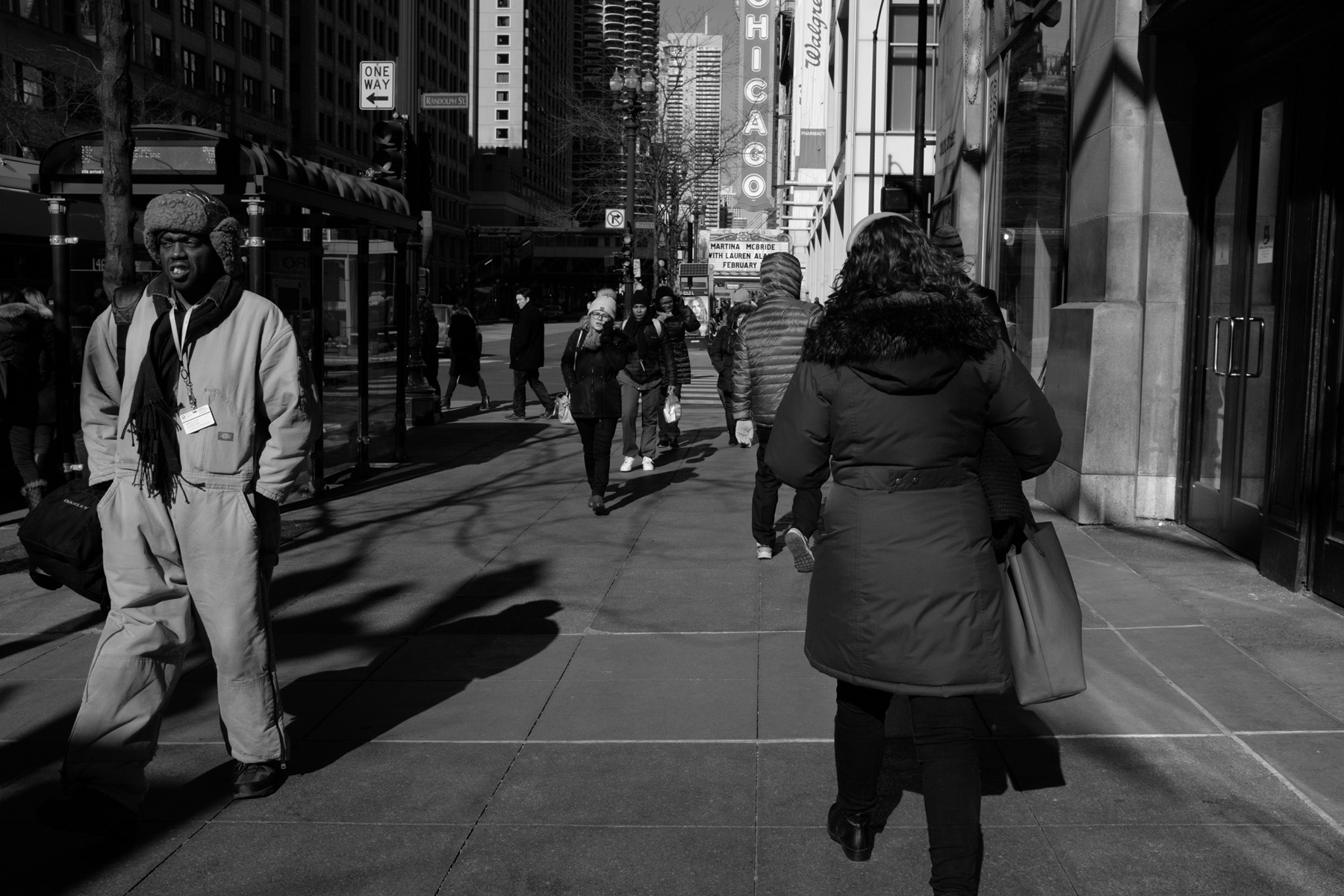a busy side walk scene in downtown Chicago in winter.