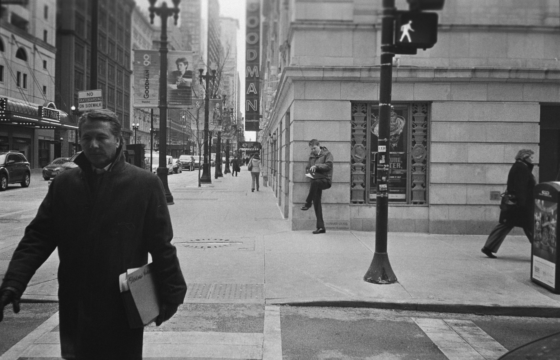 a film shot of a lawyer crossing the street in a dress winter coat, in the background you can see a man leaning up against a building looking through some documents on his knee.