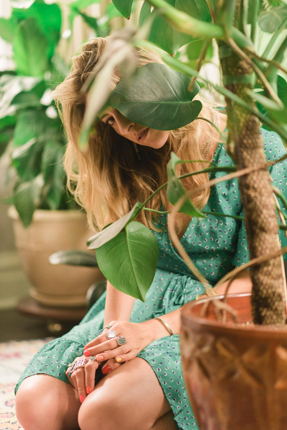 another portrait of Amanda with her plants slightly obscuring her face. she is wearing a green dress while kneeling on the floor.