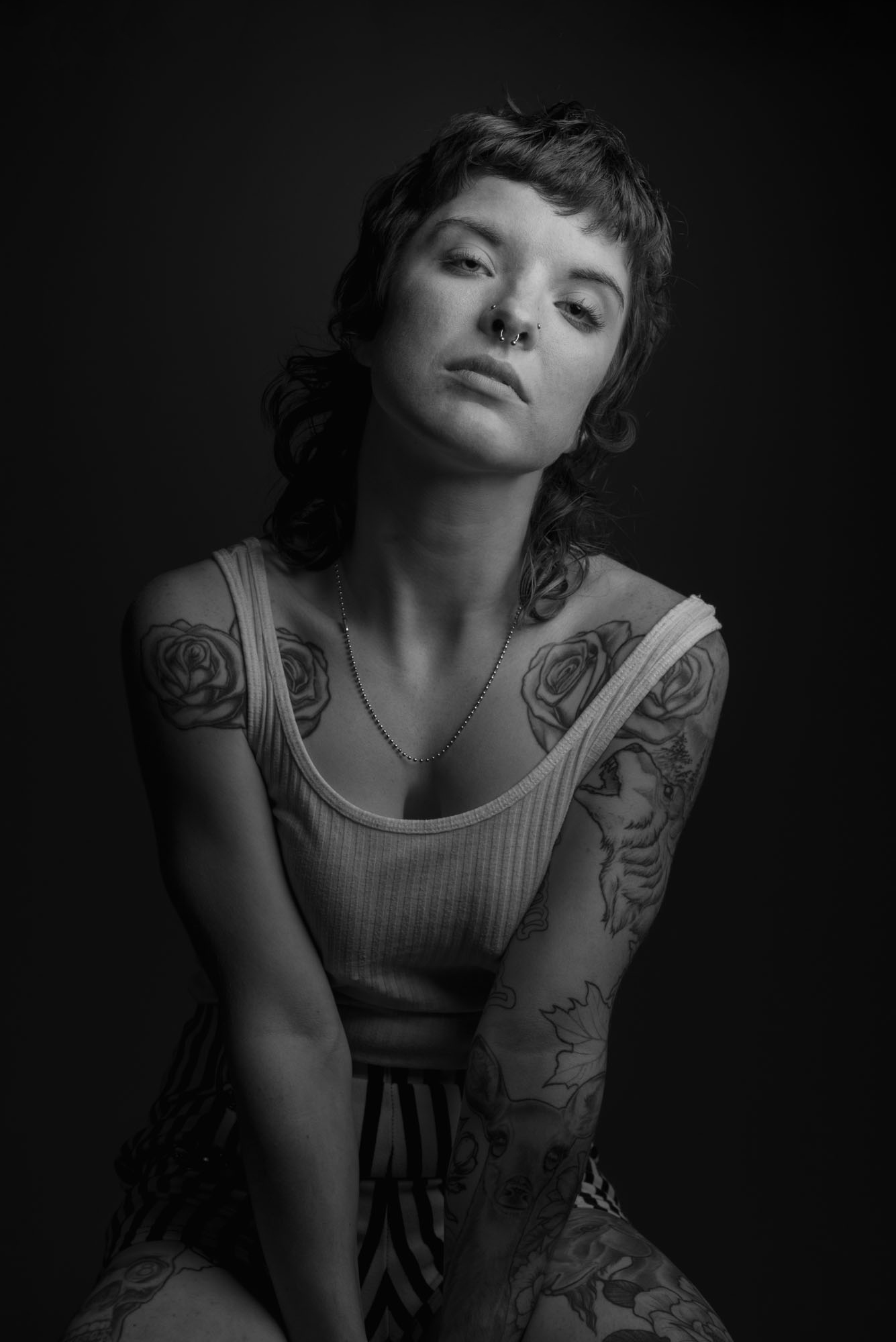 black and white portrait of Maddie wearing a white tank top and pin striped shorts.