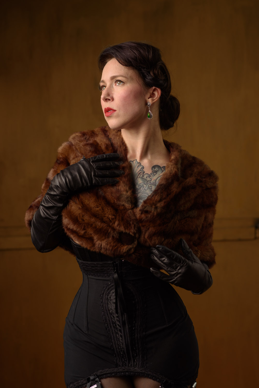 Portrait of woman wearing a fur shawl, long leather black gloves and an Edwardian styled corset in front of a copper colored backdrop.