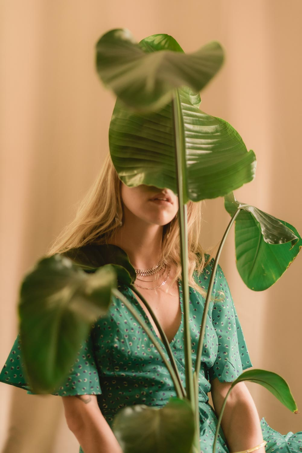 a portrait of Amanda with one of her plants covering her face partially.