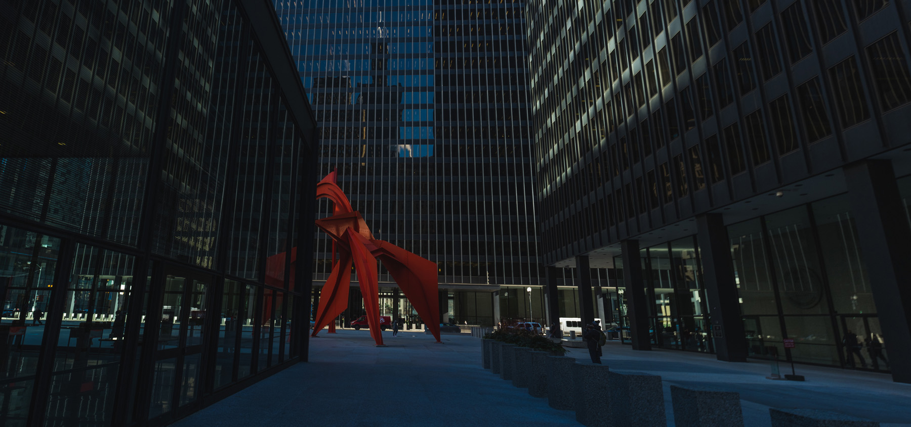 a picture of Calder's Flamingo slightly obscured by the US Post office building and you can see the Sears tower reflected on the building behind  the Flamingo.
