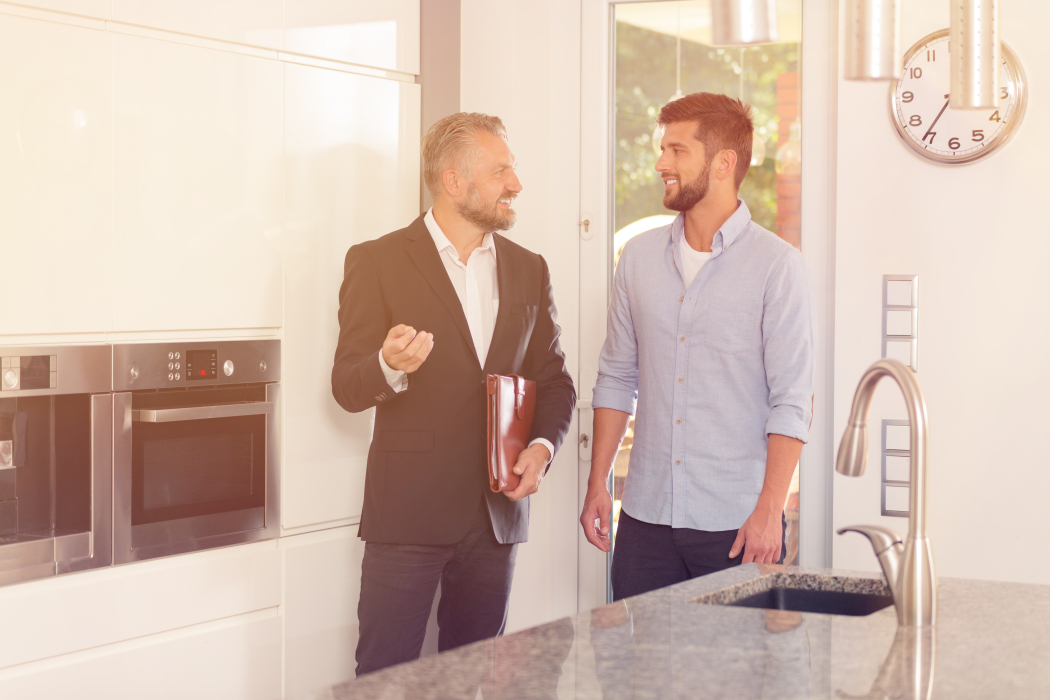 stock-photo-real-estate-consultant-talking-about-house-while-inspecting-the-kitchen-with-smiling-customer-750835114