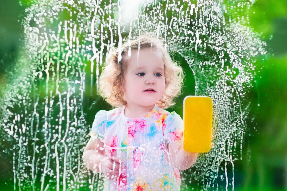 Little girl washing window