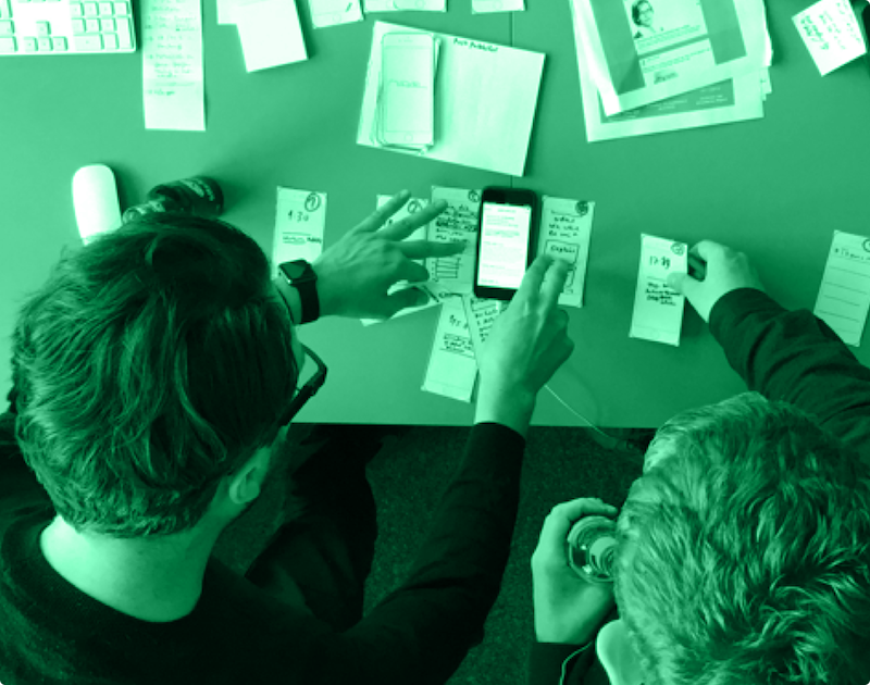 Designers working and sketching ideas using phones and paper