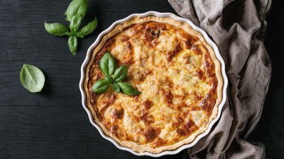 A full quiche with a sprig of basil